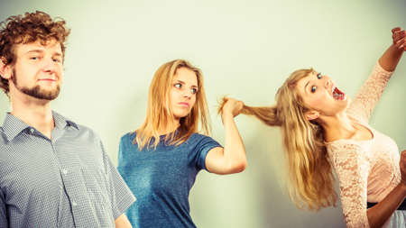 wooing: Aggressive mad women fighting over man pulling hair. Young jealous girls wooing guy. Violence.