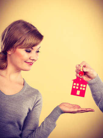 housing loan: Male hand real estate agent or husband giving woman wife new house key, keys to property owner. Housing loan concept.