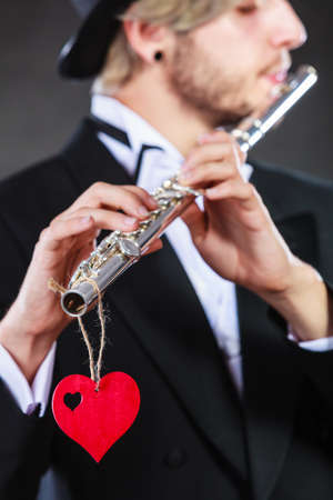Valentines day love melody concept. Flute music playing male flutist musician performer. Young elegant stylish guy with instrument and red heart Stock Photo