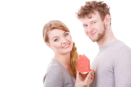Pouzdro rodina budoucnost hypotéka financí koncept. Veselý mladý pár s modelem domu. Mladistvý muž a žena s domácím symbolem.