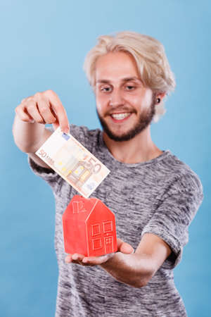Household savings and finances, economy concept. Smiling man puts money into a piggy bank in the shape of a house, studio shot on blue background