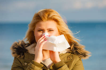 runny: Seasonal flu, cold, runny nose concept. Sneezing blonde young woman into tissue, outside sunny winter shot