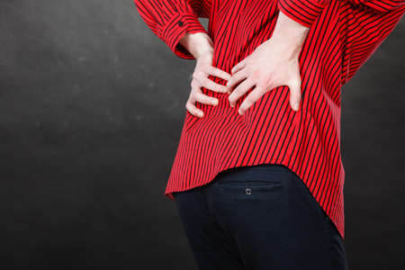 Health problems, strain on joints concept. Closeup of man in red shirt suffers from backache