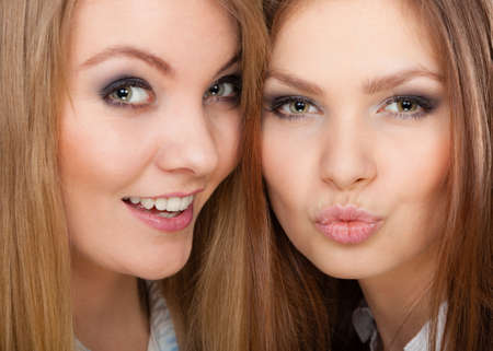 charmingly: Family relationships, friendship concept. Two beautiful women sisters, blonde and brunette with windblown hair posing charmingly. Stock Photo