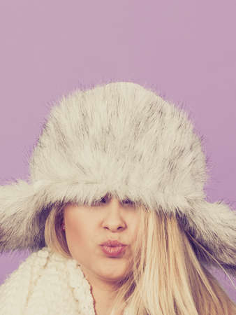 seasonal clothes: Clothing accessories, seasonal clothes concept. Woman wearing winter furry warm hat that covers her eyes Stock Photo