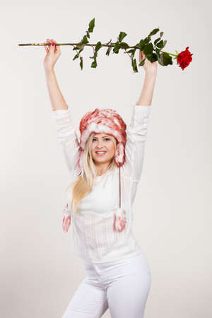 seasonal clothes: Clothing accessories, seasonal clothes concept. Woman wearing winter furry warm hat holding romantic red rose.