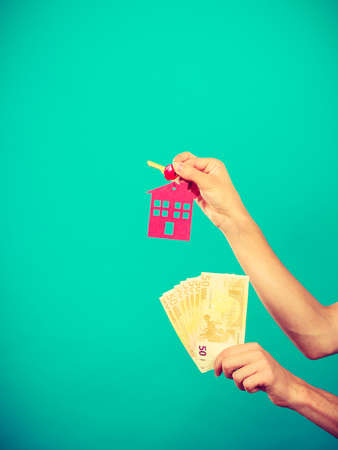 Household savings and finances, economy concept. Person holding money and keys to house, studio shot on blue background Stock Photo
