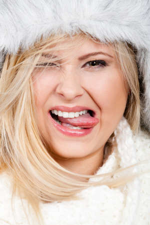 seasonal clothes: Clothing accessories, seasonal clothes concept. Portrait of woman wearing winter furry warm hat sticking her tongue out. Stock Photo