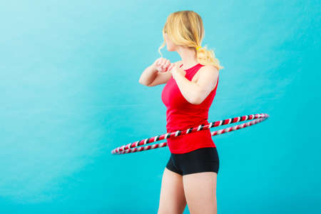 Fitness, activity, healthy lifestyle. Young blond woman doing exercise with hula hoop, on blue Stock Photo