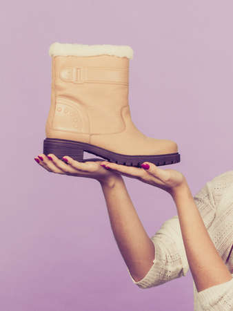 seasonal clothes: Seasonal clothes concept. Woman hand holding winter warm beige boots