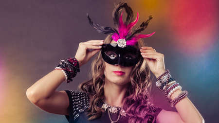 Holidays, people and celebration concept. Woman with carnival venetian mask on colorful background. Stock Photo