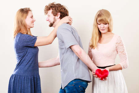mislead: Betrayal and infidelity concept. Handsome boy with two attractive blondie girls. Man cheating women by mislead chosen one and offer his heart to another.