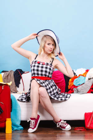 Packing problems, necessary things during the trip concept. Woman sitting on sofa holding sun hat, getting ready for vacation, choosing clothes to pack into suitcase