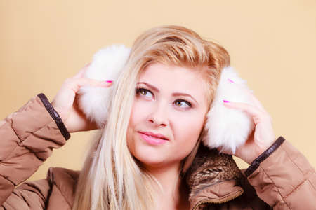 Accessories and clothes for cold days, fashion concept. Blonde woman in winter warm earmuffs and jacket.