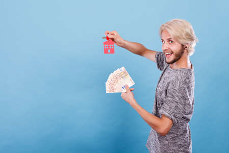 Household savings and finances, economy concept. Happy man holding money and keys to house, studio shot on blue background Stock Photo
