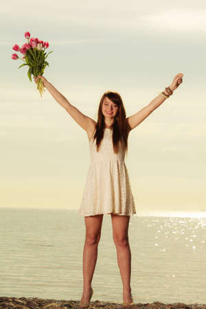Travel, romance concept. Attractive woman wearing white short dress, smiling and holding bouquet of tulips above her head on beach with sea in background
