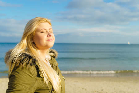 Ocio, pasar el tiempo libre fuera, sano concepto camina. La mujer llevaba chaqueta caliente relaja en la playa cerca del mar, día soleado frío