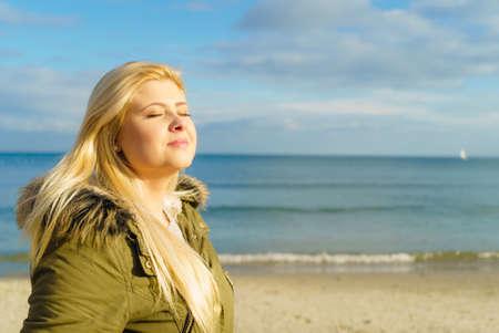 Vrije tijd, vrije tijdbesteding buiten, gezonde wandelingen concept. Vrouw draagt warme jas ontspannen op het strand in de buurt van de zee, koude zonnige dag
