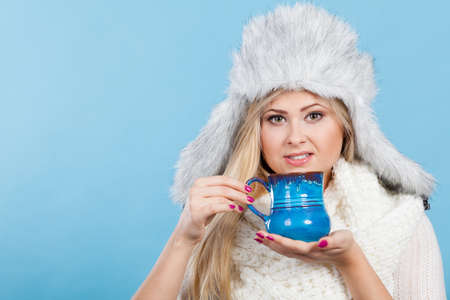 seasonal clothes: Clothing accessories, seasonal clothes concept. Woman wearing red jumper and winter furry warm hat holding and drinking hot drink from mug