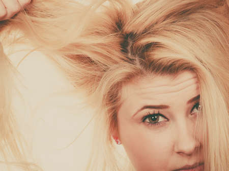 damaged: Hair care mistakes, bleaching problems concept. Blonde woman holding her dry, damaged hair.