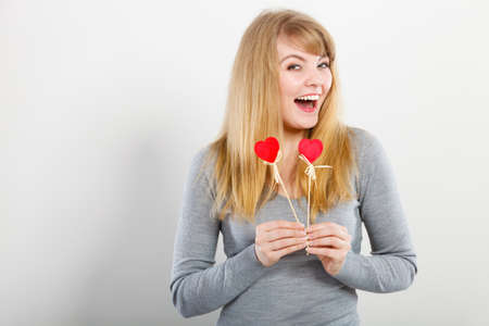 Love and fun concept. Lovely enjoyable smiling woman playing with two little red hearts on sticks. Playful joyful attractive blonde girl portrait. Stock Photo