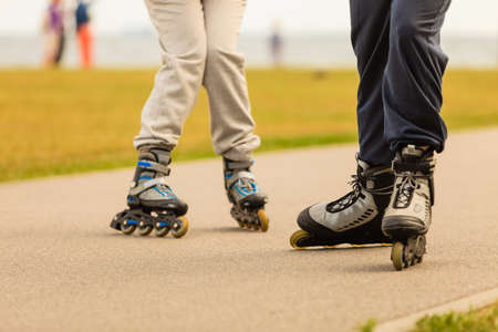 roller blade: Active holidays, exercises, sport concept. Man and woman wearing roller blades on the street, no face