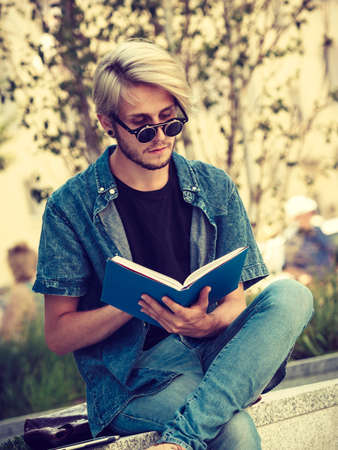 outsider: Male fashion, student concept. Guy holding and studying from notebook wearing jeans outfit and eccentric sunglasses sitting on white ledge Stock Photo