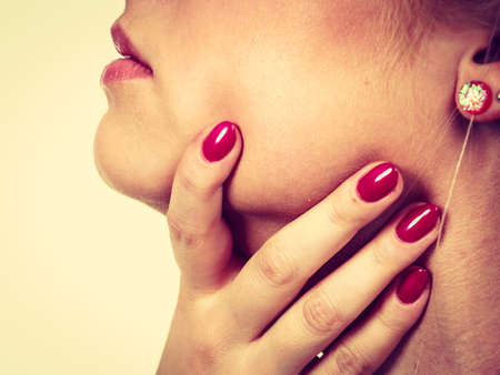 endocrinology: Sore throat, tonsillitis, health problems concept. Woman holding her neck, feeling pain.
