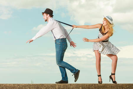 holidays love relationship and dating concept - romantic playful couple retro style flirting playing on sea shore, guy running from his girlfriend Stock Photo