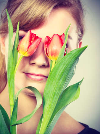 Beauty nature flora symbolism concept. Blonde girl blinded by flowers. Young female covering her eyes with tulips. Stock Photo