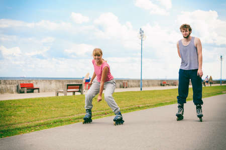rivals rival rivalry season: Exercising and competition in sport. Healthy lifestyle and wellbeing. Summertime hobby. Young people race together on rollerskates having fun. Stock Photo