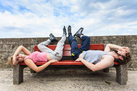 outdoor training: Young tired people friends in training suit with roller skates. Woman and man relaxing lying on bench outdoor. Stock Photo