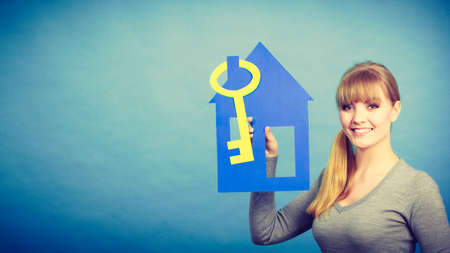 Plans ideas and concepts for future. Young joyful blonde woman with house and big key. Charming girl enjoy her decision of buying real estate.