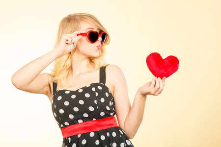 Woman blonde lovely girl wearing dotted dress sunglasses holding red heart love symbol studio shot on bright. Valentines day happiness concept Stock Photo