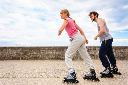 Exercising and competition in sport. Healthy lifestyle and wellbeing. Summertime hobby. Young people race together on rollerskates having fun. Stock Photo