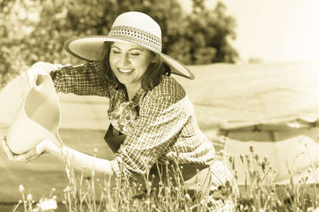 Gardening. Attractive woman in hat working in her backyard garden watering flowers outdoor Stock Photo