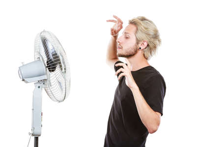 Air conditioning, heat, artistic concept. Young man in front of cooling fan, artistic way, studio shot isolated.