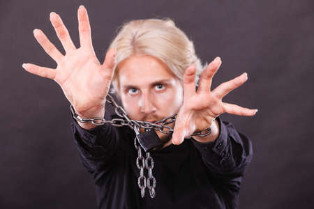 aghast: No freedom, social problems concept. Furious man with chained hands, studio shot on dark grunge background Stock Photo