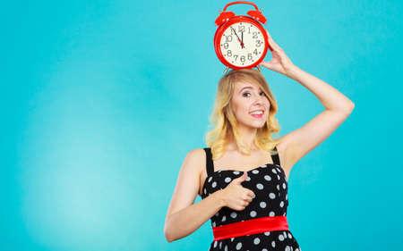 puntualidad: concepto de tiempo de gestión. Muchacha rubia con un vestido negro de puntos expresión sonriente cara con el reloj de alarma en azul. Foto de archivo
