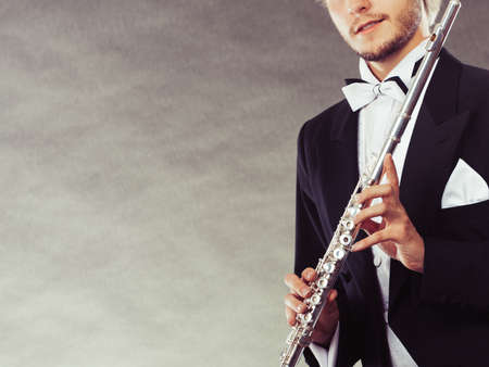elegantly: Classical music, passion and hobby concept. Elegantly dressed musician man holding flute. Studio shot on dark grey background Stock Photo