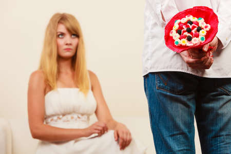 apologize: Man with candy bunch flowers behind back and pretty unhappy bored woman. Boyfriend with present gift trying to apologize girlfriend. Stock Photo