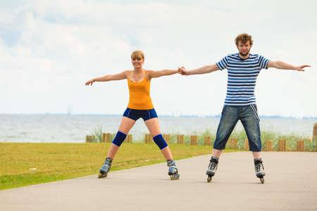 Estilo de vida activo personas y concepto de libertad. Young fit par en patines de ruedas montando al aire libre en la costa del mar, mujer y hombre patinar disfrutando de tiempo juntos