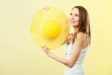 head protection: Holidays summer fashion and head protection. Woman in big yellow hat. Portrait of charming female on bright background.