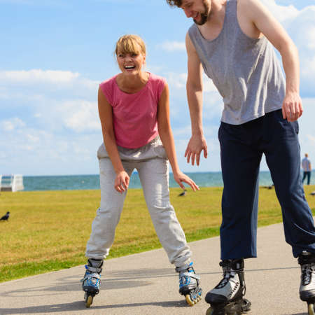 rollerskates: Love dating leisure romance relax concept. Cheerful couple enjoying ride together. Young girl and boy skating on rollerskates in park near sea.