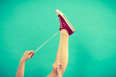 Footwear, fashion, shoes concept. Person tying laces in red sneaker with foot up, studio shot on blue green background