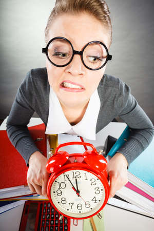puntualidad: Paper work against time. Young expressive woman in office with big red clock. Unhappy businesswoman so far to ending her work. Foto de archivo