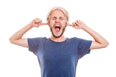 decibel: Stressful unpleasant situation conflict. Angry mad young man plug closing ears with fingers, protecting from loud noise. Guy not wanting to listen, isolated on white