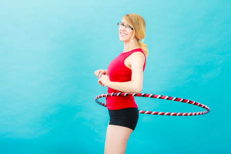 Fitness, activity, healthy lifestyle. Young blond woman doing exercise with dance hoop, on blue