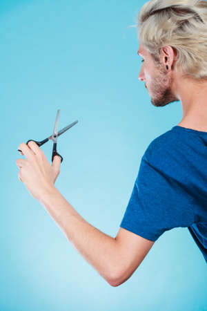 Coiffure hairstyle and haircut. Young cool guy holding special shears tool for work of hairdresser, on blue Stock Photo