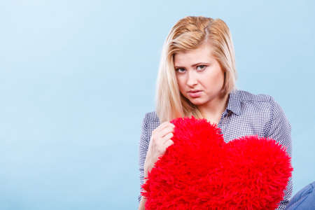 desilusion: Break up, divorce, bad relationship concept. Sad, depressed woman holding big red fluffy pillow in heart shape, she needs love.